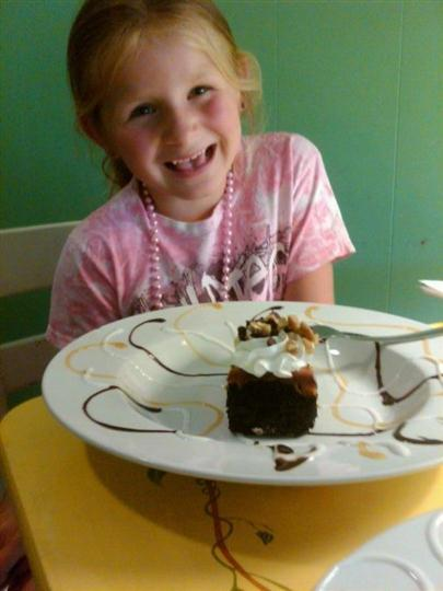 Young girl smiling at the camera with a cake in front of here.