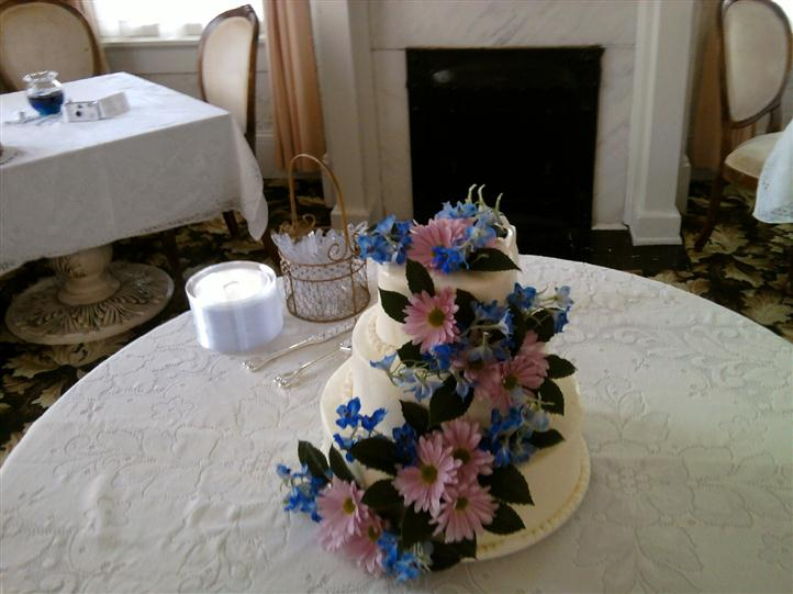 Three tiered white cake with pink an blue flowers.