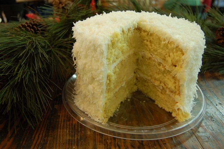 Three layer cake with coconut on the outside.