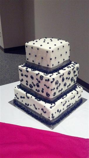 Three tier white square cake with navy blue dots and designs.
