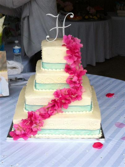 Four tier square white cake with light blue strips and pink flowers.