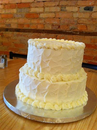 Two tier cake with vanilla and light yellow frosting.