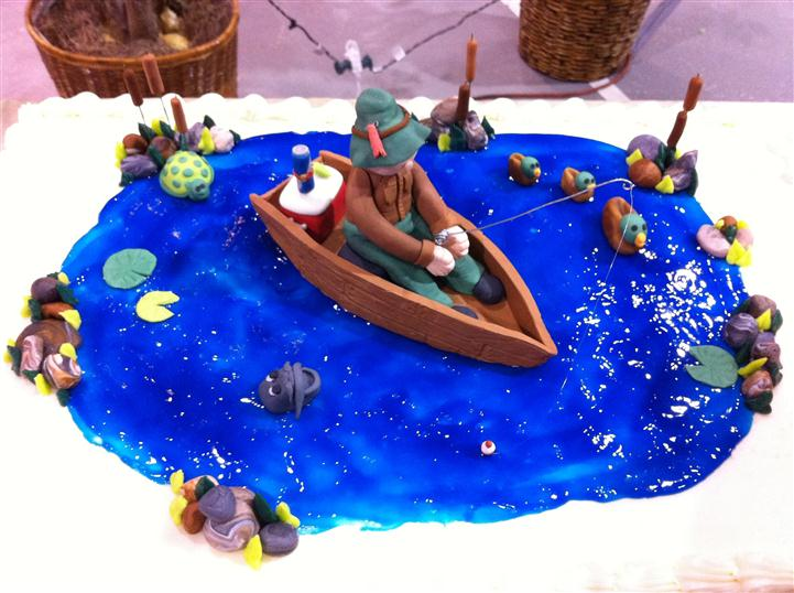 White cake with blue icing representing a pond with a man in a boat on top.