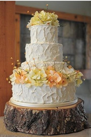 Four tier white round cake with yellow and orange flowers.