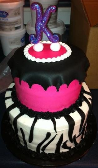 Two tier cake that is black, bright pink and white with the letter K on top.
