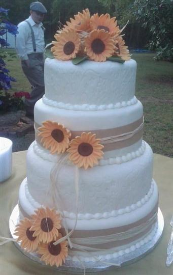 Three tier round white cake with orange sunflowers.