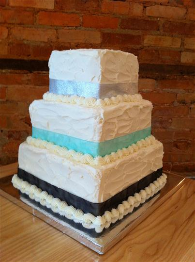 Three tier square cake with silver, light blue and black strips.