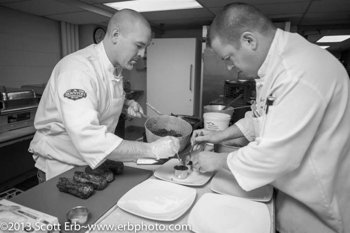 Two chefs preparing dinner on four glass plates