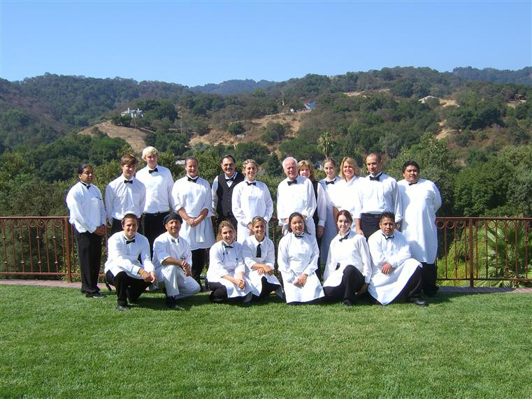Staff posing for photo in front of scenic hills