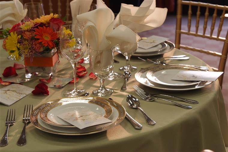 table setup with utensils, plates and flowers