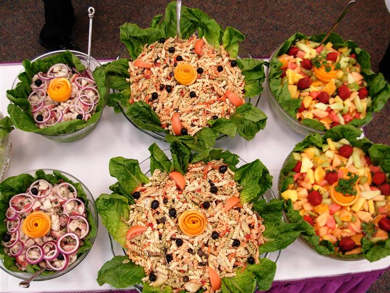 catering display of sliced fruit and salads in bowls on a table