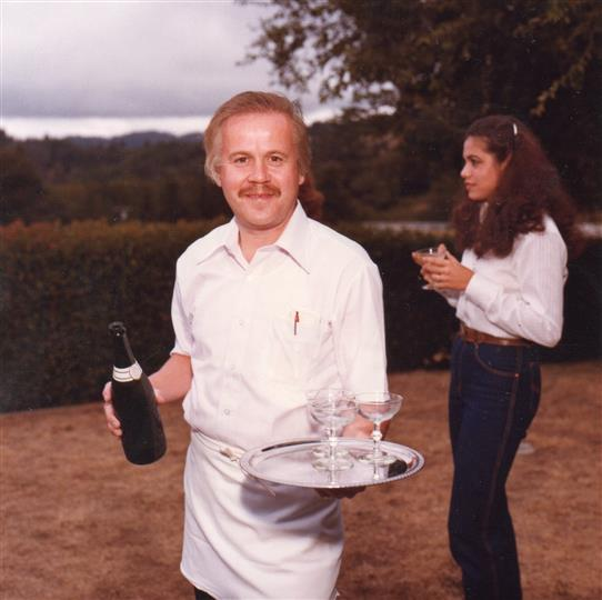 Gunther Meyberg holding wine bottle and wine glasses on tray