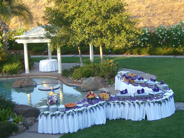 wedding buffet catering of metal trays next to a pool outdoors