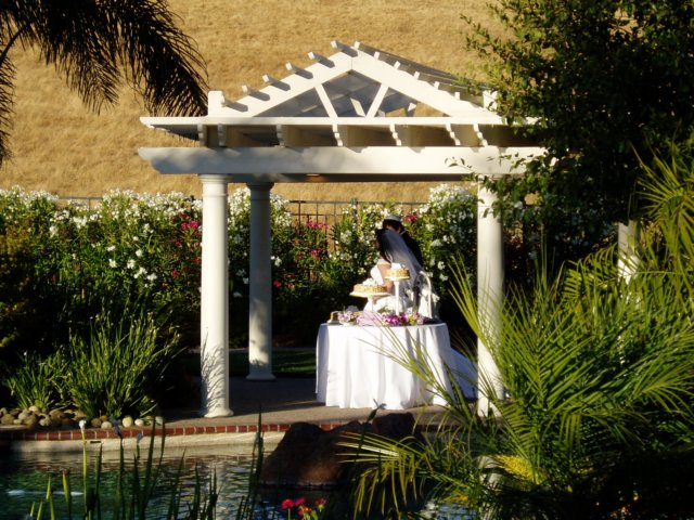 Bride and groom under gazebo structure in garden