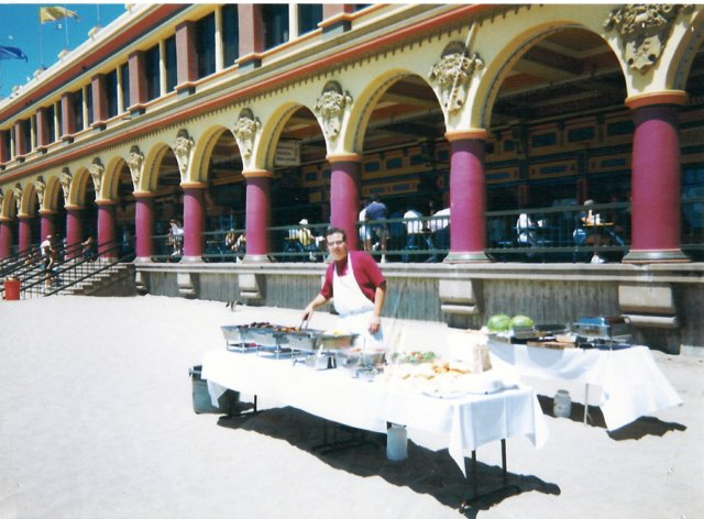 Man at catering table in front of large venue