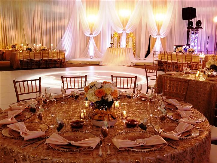 Wedding venue with elegant reception stage and covered tables.