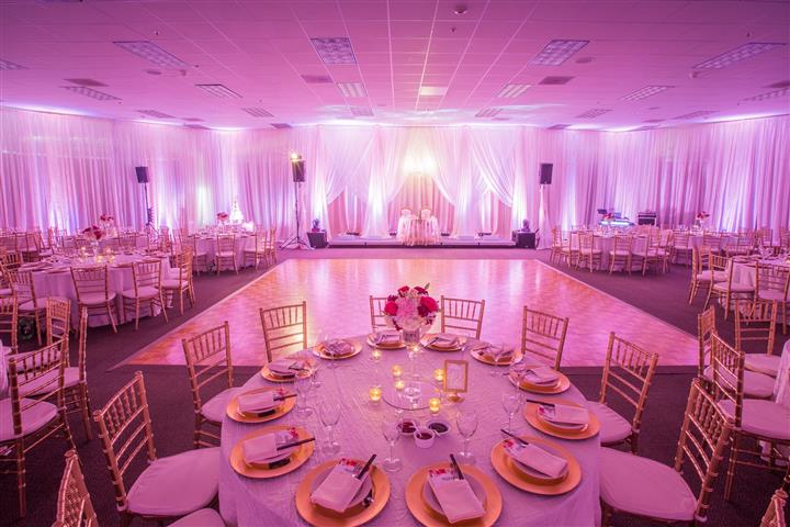 Wedding venue indoors with dance floor and covered tables