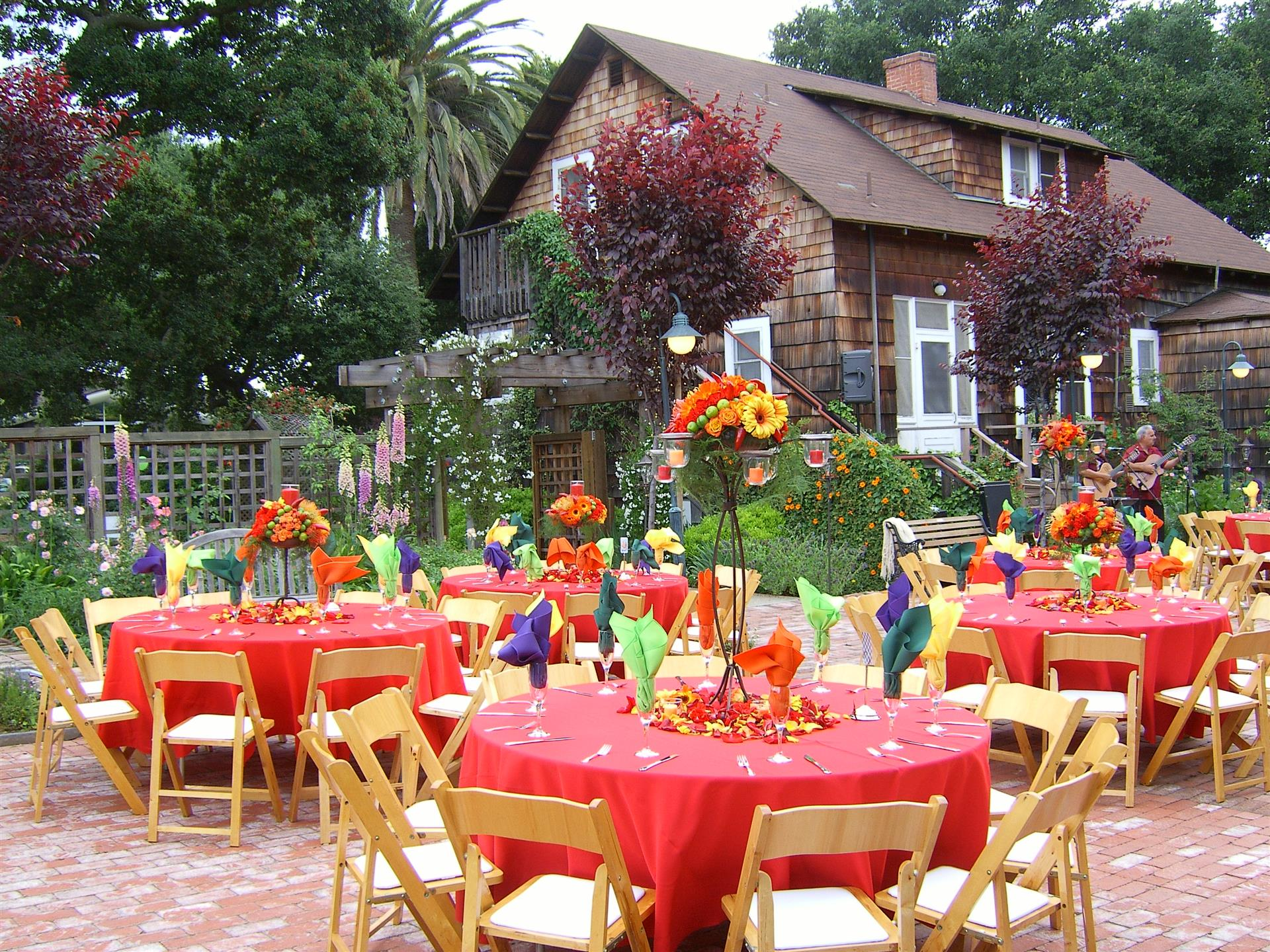 outdoor tables with flowers and placesettings on a patio