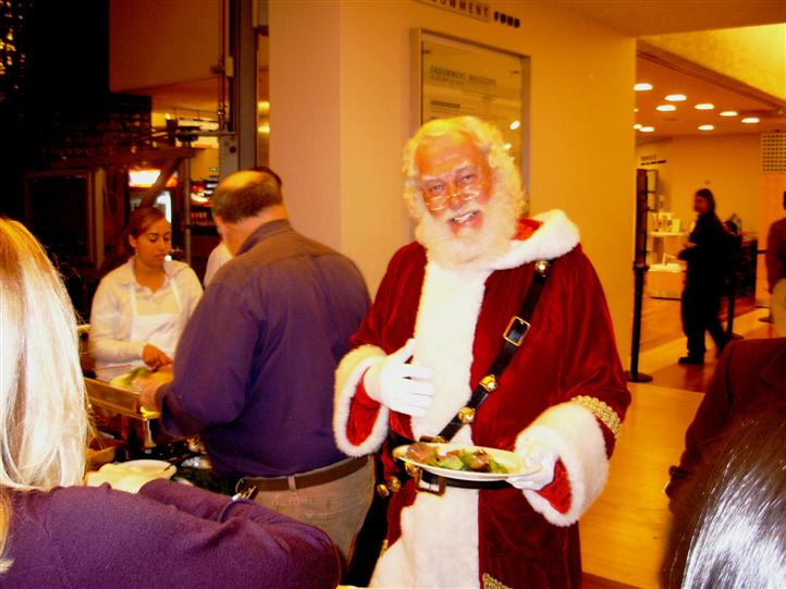 Man dressed in santa costume getting food with other people