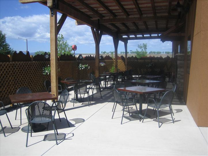 Outdoor patio with square tables and metal chairs