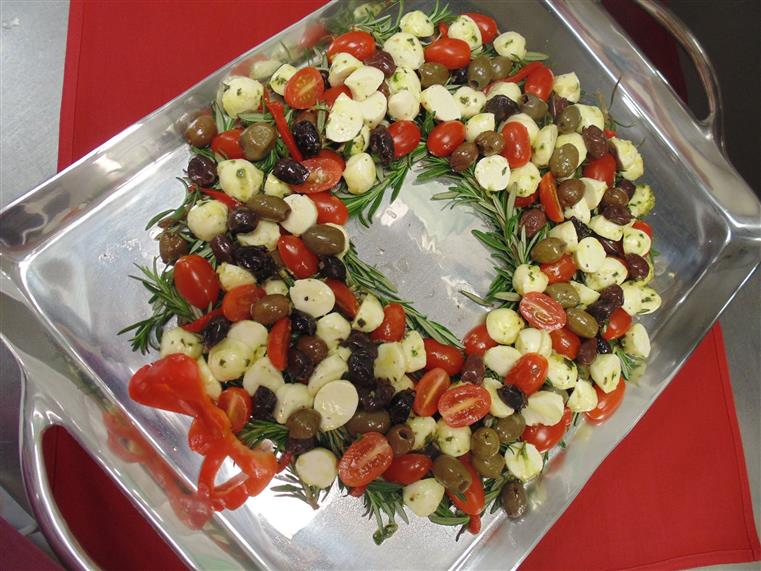 Various olives and round cheeses in the shape of a wreath