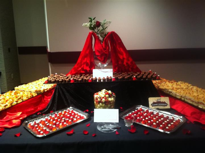 Table decoarted with various chocolates and fruit and a rose centerpiece