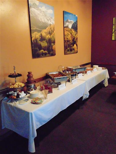 Assortment of cheese, fruit dessert and other food set up on table in various sized trays and dishware