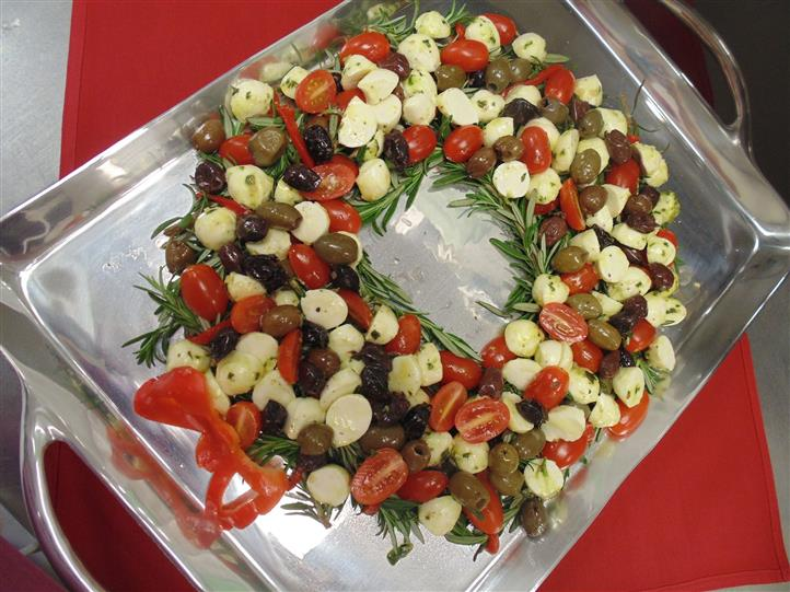 Assrtment of olives and round cheeses in the shape of a wreath