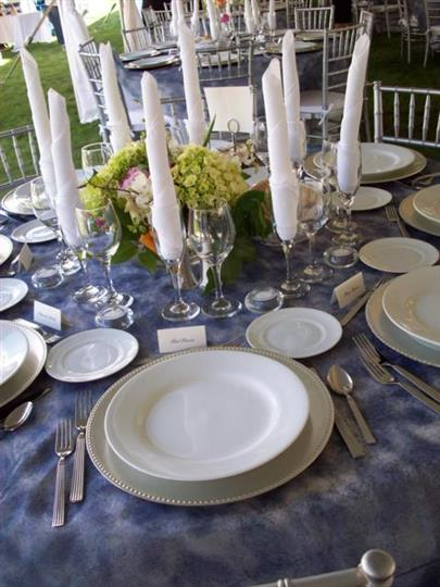 Table set with dishware, silverware andchampagne glasses stuffed with decorative napkins
