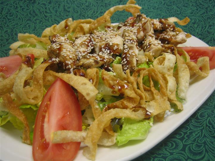 Salad layered with wontons, chicken, and drizzled in sauce and sesame seeds