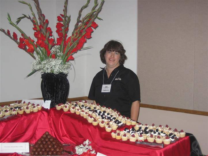 Woman standing infront of table with assortment of small desserts