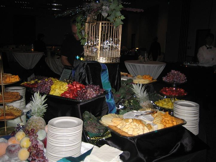 Assortment of cheese, fruit, crackers and silverware on table