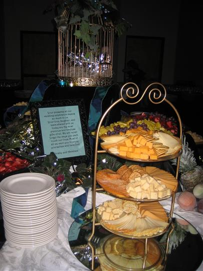 Assortment of cheese and crackers on table next to stack ofplates