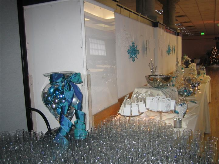 Table holding wine glasses and various vases and glassware containing candy and decorations