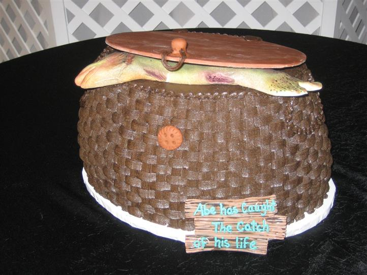 "Cake decorated with a fake fish and sign reading ""Abe has caught the catch of his life"""