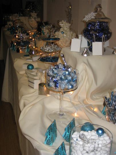 Table holding various vases and glassware containing candy and decorations