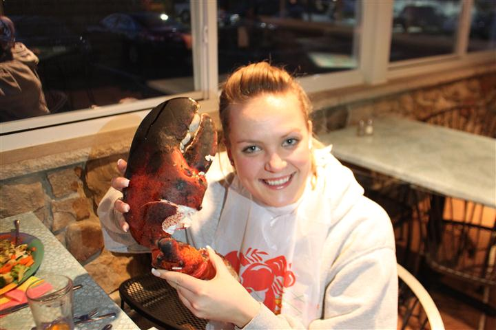 female smiling and holding lobster