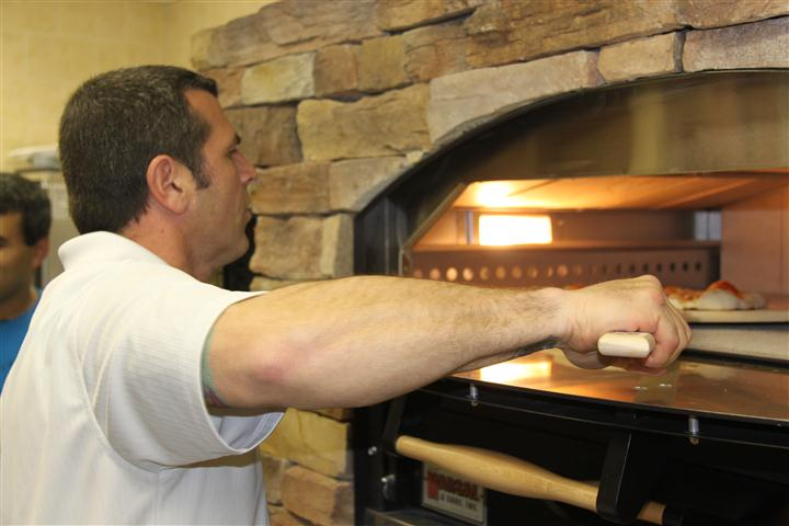employee getting food out of oven