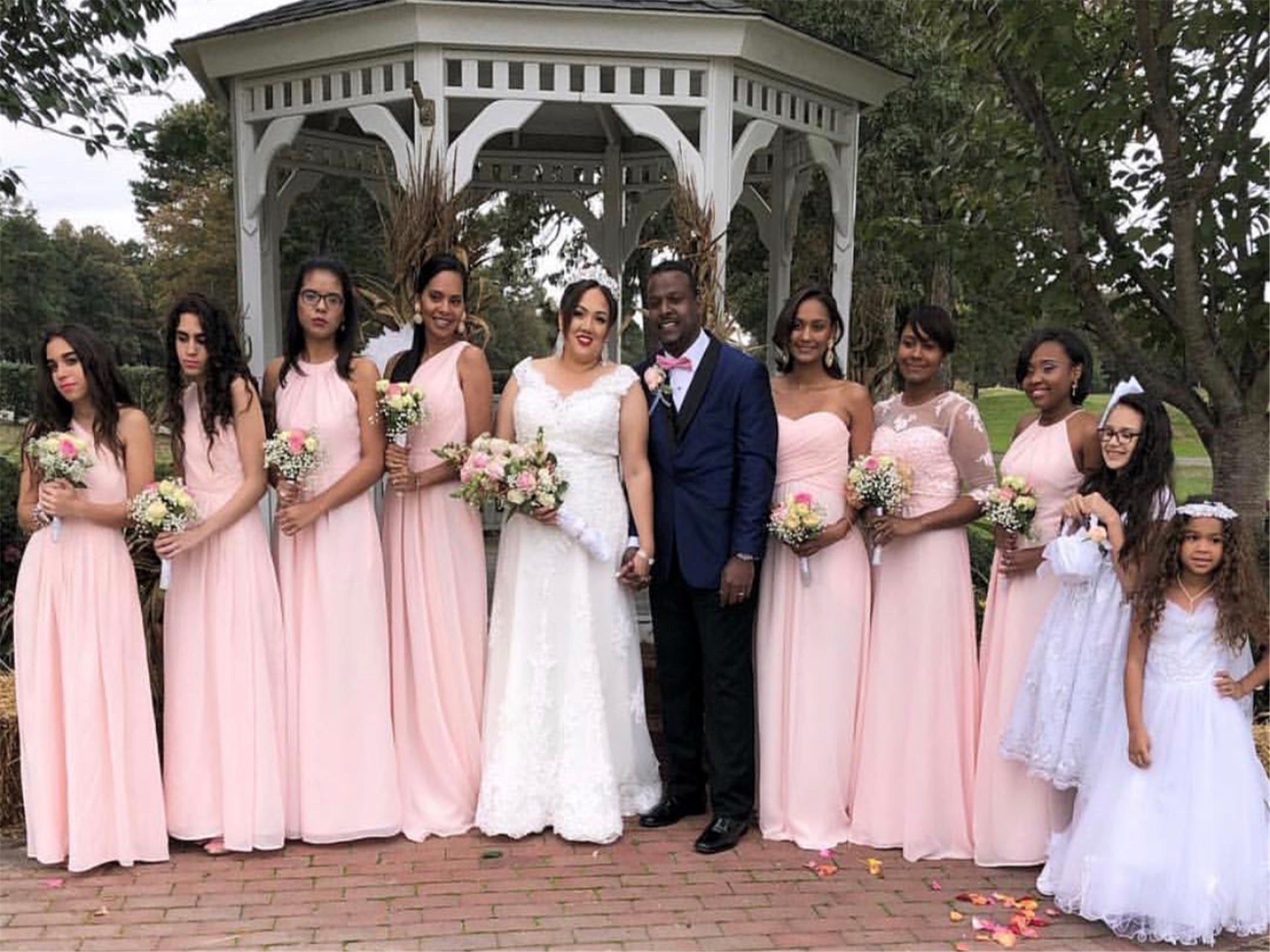 husband and wife standing with bridesmaids