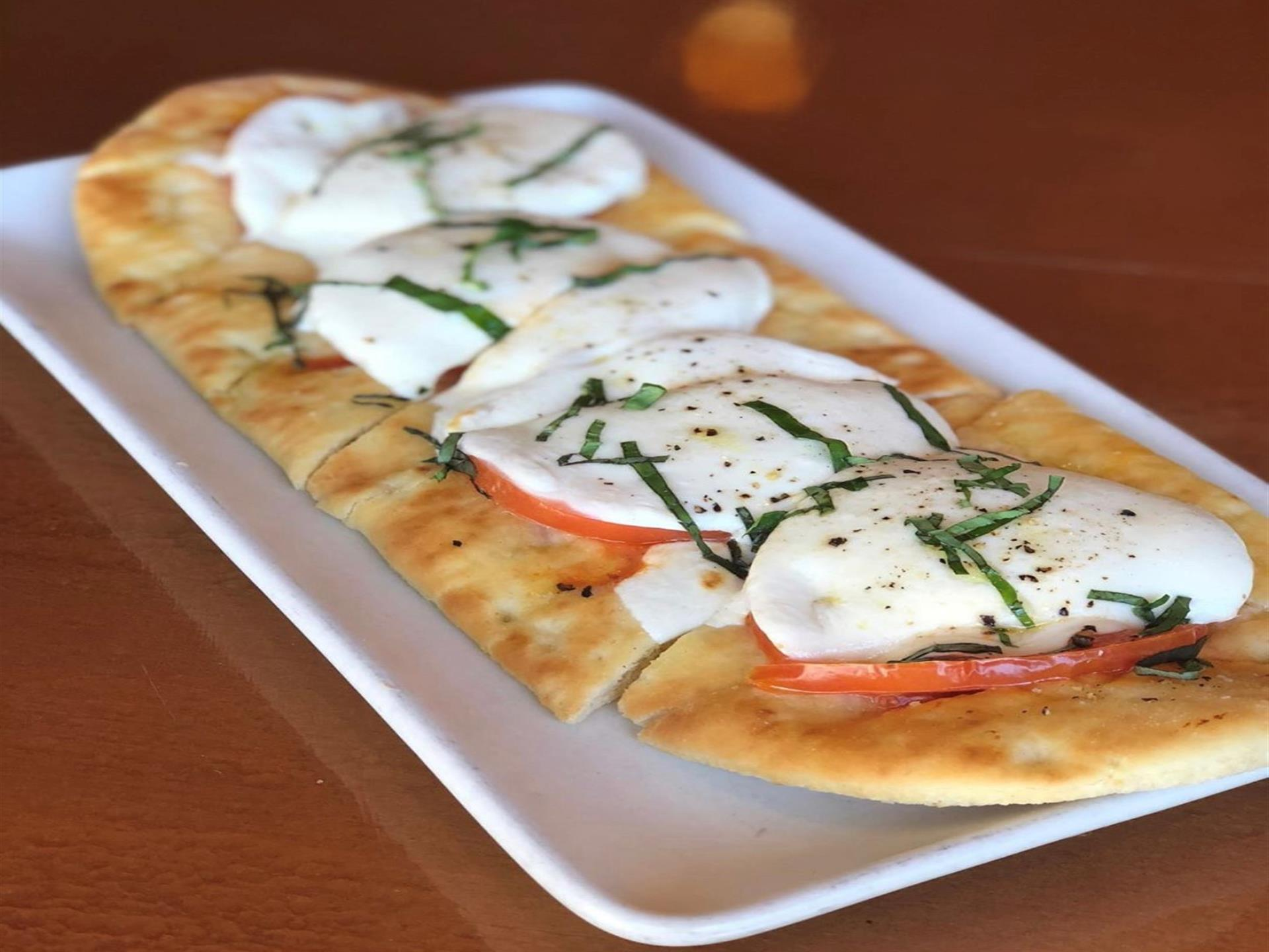 A flatbread with cheese and tomato on it