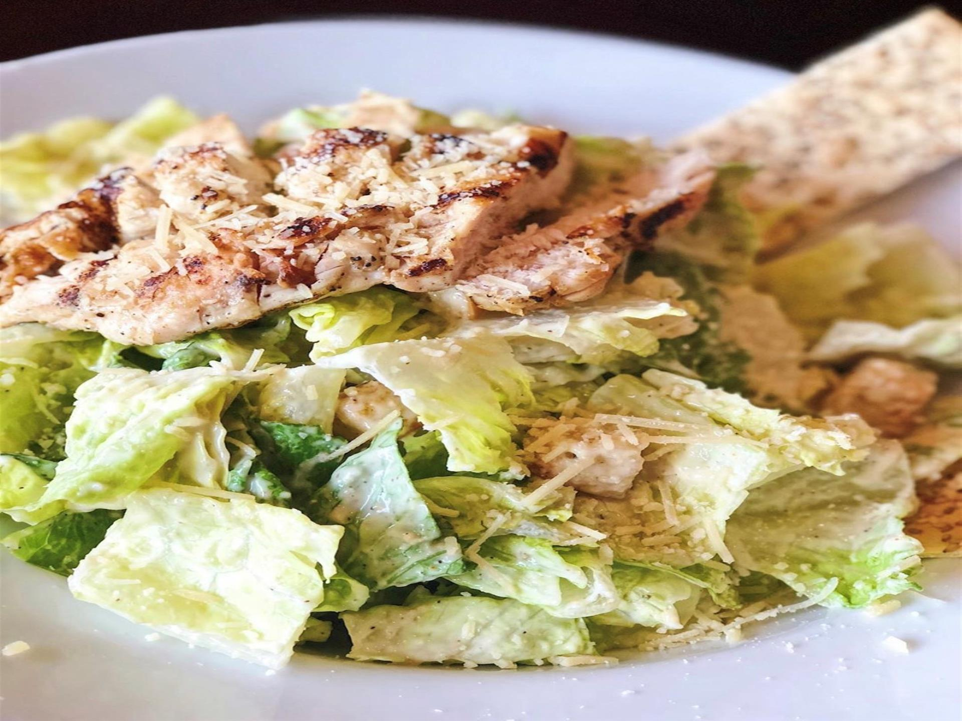 A grilled chicken caesar salad close up.