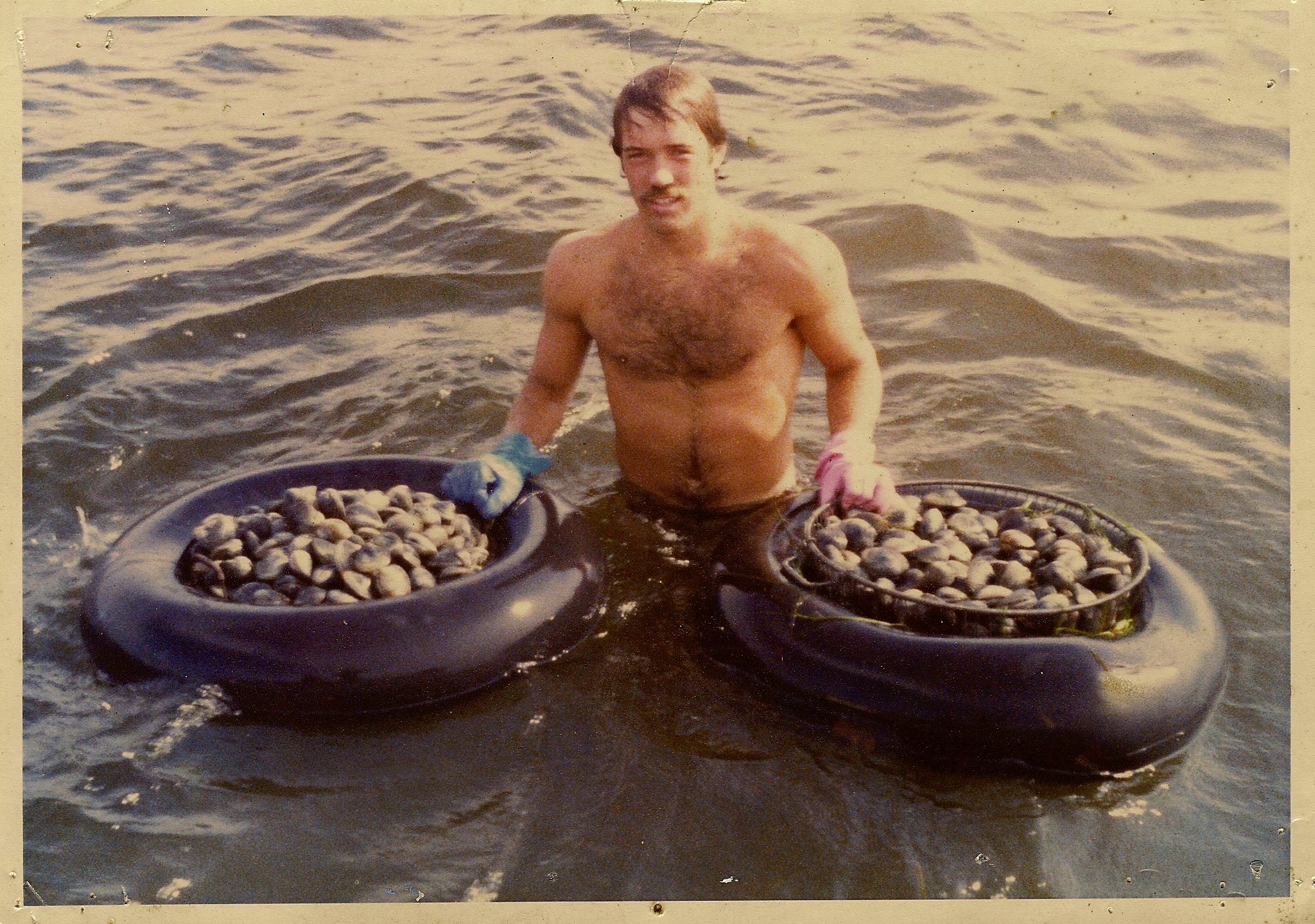man in ocean with buckets of clams