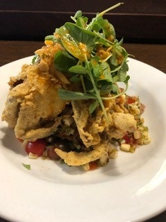 Batter dipped fried crabs atop roasted corn salsa topped with fresh watercress.