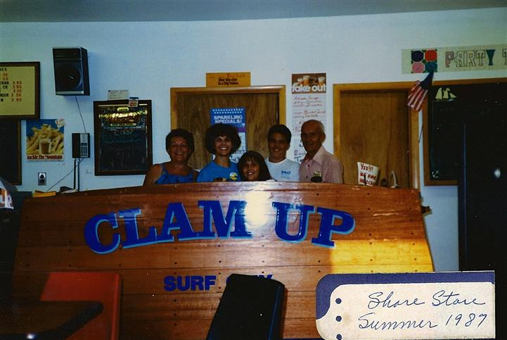 five employees standing behind counter with words clam up