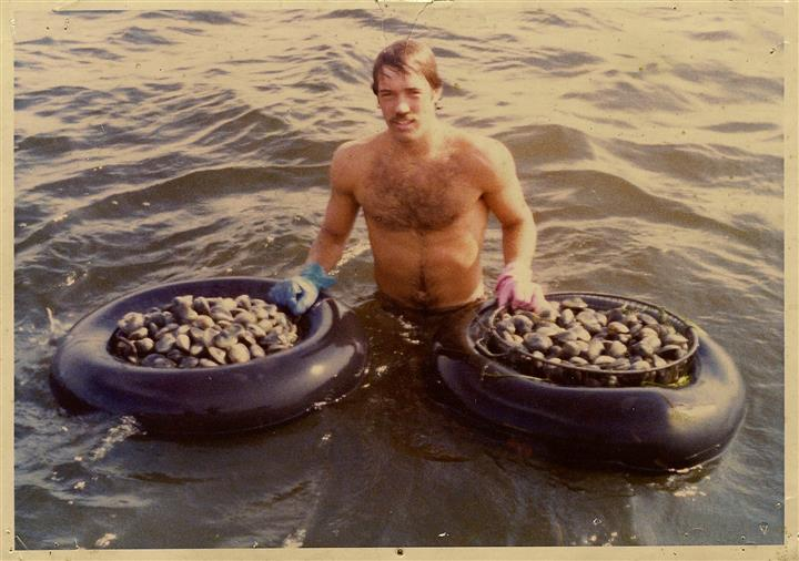 man in water holding buckets of clams