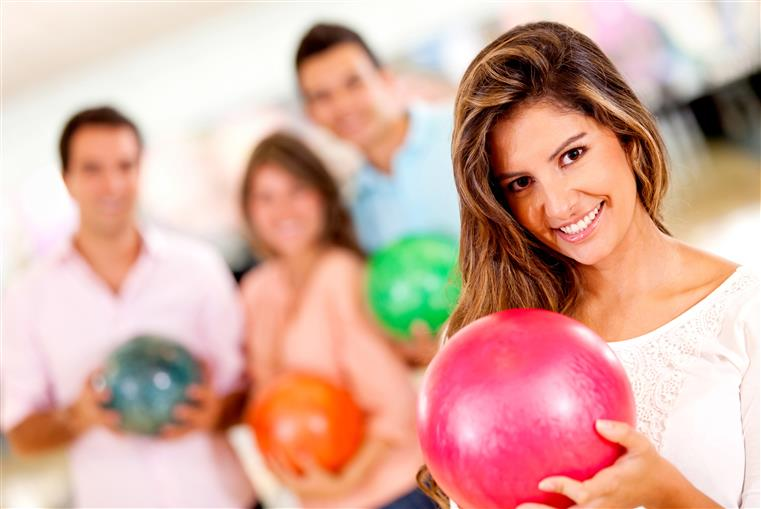 female holding bowling ball with people in background