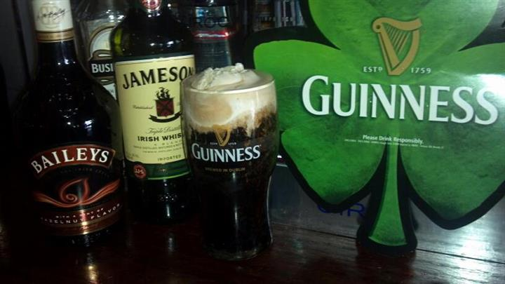 A glass of Guinness at the bar beside a bottle Baileys and a bottle of Jameson