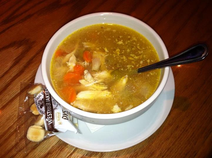 A bowl of soup with chicken and carrots