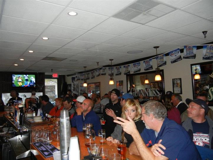 The bar full of people watching a football game
