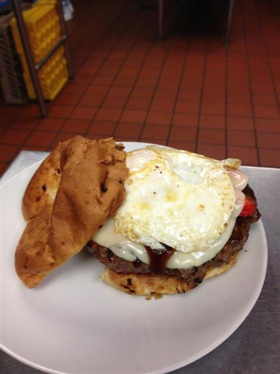 An open faced burger topped with Applewood smoked bacon, sharp cheddar and a fried egg